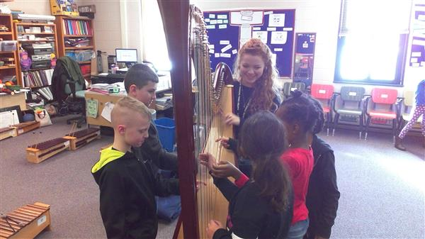 Students playing harp with our guest musician!